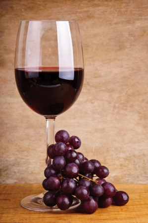 glass of red wine and grapes on a vintage wooden background photo