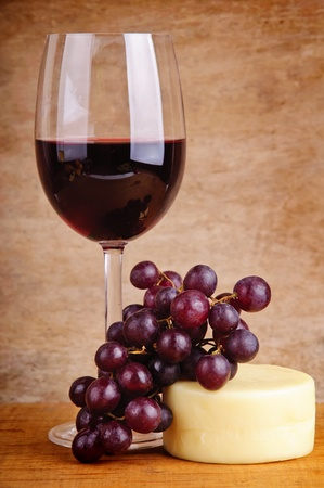 still life with glass of red wine, grapes and cheese on a wooden vintage background photo