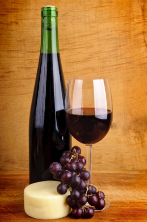 still life with red wine, cheese and grapes photo