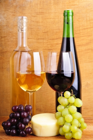 still life with cheese, wine and grapes on a vintage wooden background photo