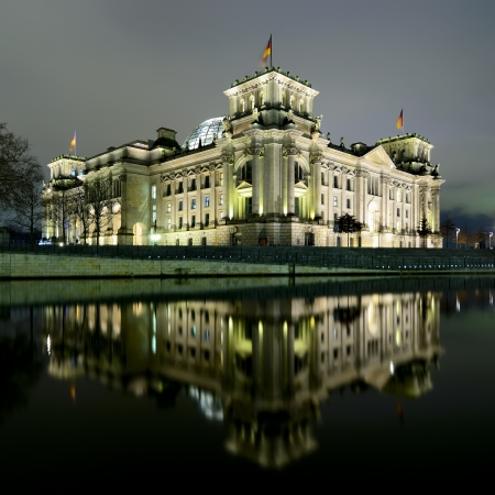 reichstag (bundestag) with reflection in spree river in berlin, germany at night