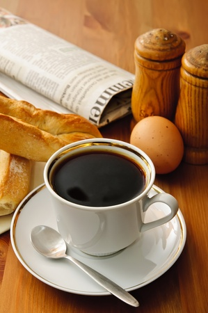 breakfast with cup of coffee and newspaper, croissant, egg, salt, pepper photo