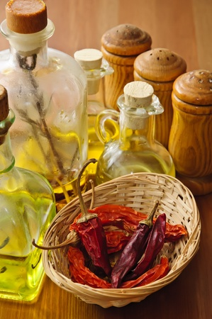 dried chili with olive oil and condiments on a wooden background