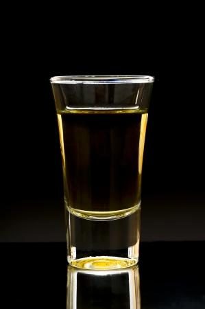 sparo: whisky o tequila girato su uno sfondo scuro Archivio Fotografico