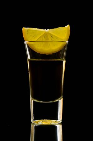 tequila shot with lemon isolated on a black background photo