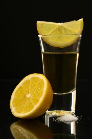 tequila geschoten met citroen en zout op een zwarte achtergrond