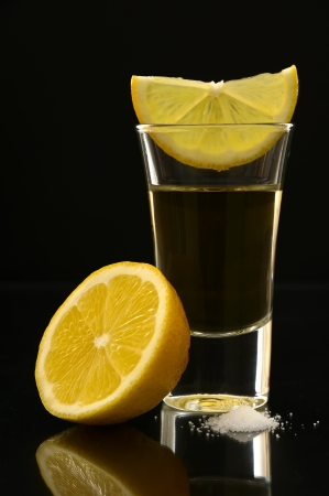 tequila: tequila shot with lemon and salt on a black background
