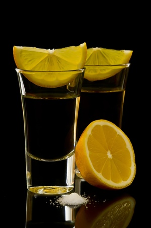 two tequila shots with lemon and salt on a black background photo
