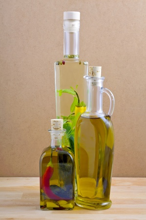 flavoring: bottles of herbal and olive oil on a wooden background