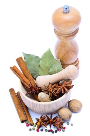 mortero: especias diferentes con molinillo de pimienta, mortero aislado en un fondo blanco Foto de archivo