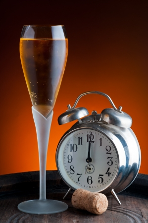 glass of champagne and old watch showing twelwe o´clock photo