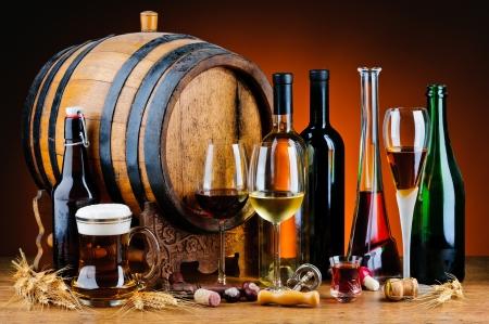 Stilleben mit verschiedenen alkoholischen Getränken und Holzfass