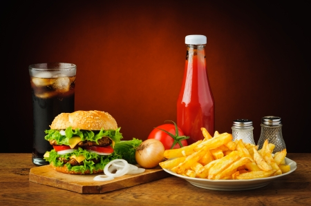 still life with hamburger menu, french fries, cola drink, tomato ketchup, salt and pepper