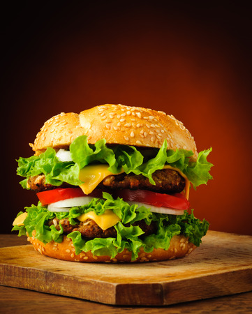 hamburgers: traditional homemade tasty hamburger or cheeseburger on a wooden plate Stock Photo