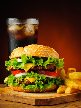 cheeseburger: still life with traditional hamburger, frech fries potatoes and cola drink Stock Photo