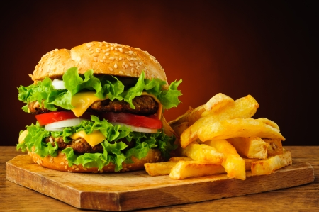 Todavía vida con la hamburguesa tradicional y papas fritas francés