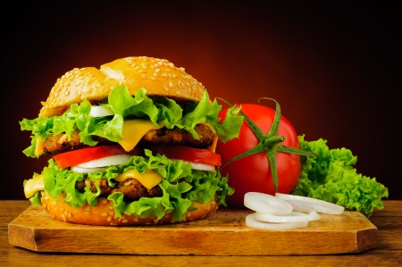 american cuisine: still life with double cheeseburger or hamburger and fresh vegetables
