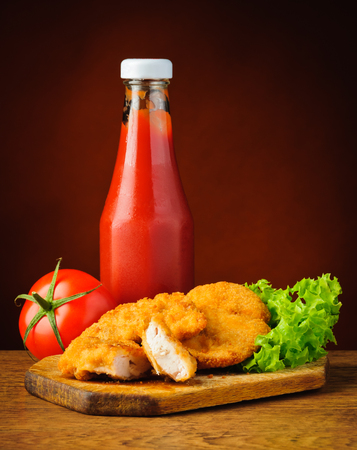 nuggets pollo: Bodeg�n con frescos nuggets de pollo frito y salsa de tomate