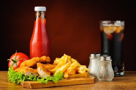 still life with fast food menu, chicken nuggets, french fries, cola and tomato ketchup photo