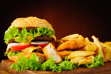chicken burger: still life with traditional cheeseburger, fried chicken nuggets and french fries Stock Photo