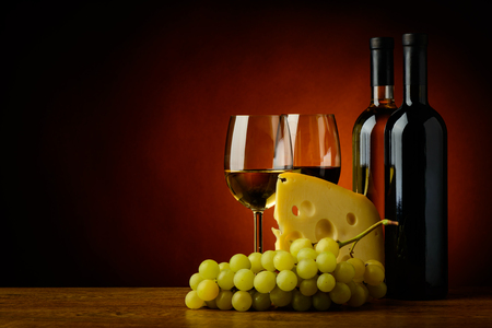 still life with cheese, grapes, red and white wine photo