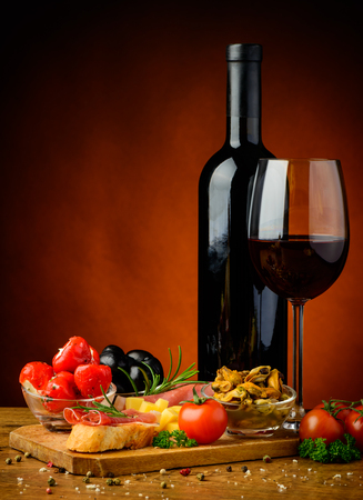 still life with spanish tapas, glass and bottle of red wine photo