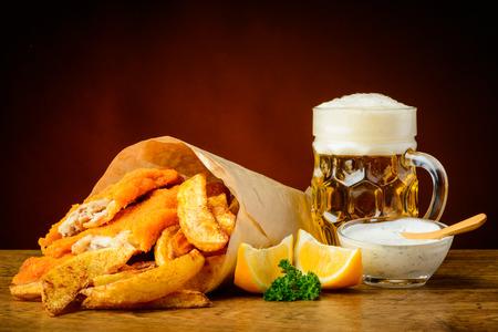fish and chips: naturaleza muerta con pescado, elaboración casera, patatas fritas y cerveza Foto de archivo