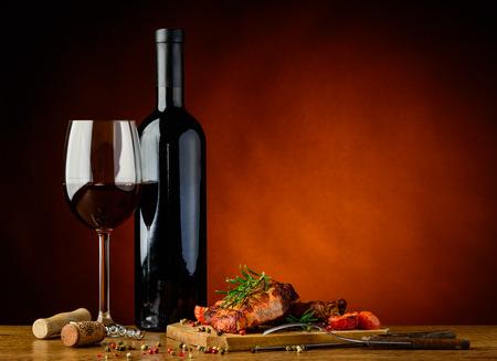 グルメ向きのロマンチックなディナーのある静物焼きステーキと赤ワイン
