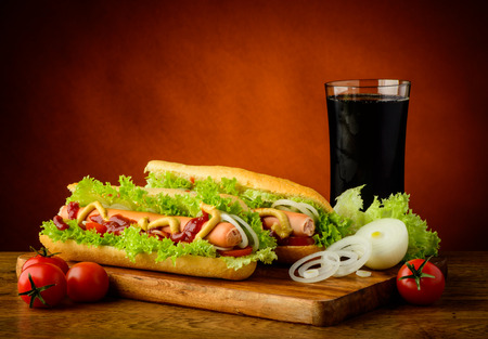 hotdog: still life with traditional hotdog menu, cola drink and vegetables Stock Photo