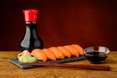 still life with nigiri sushi with salmon, soy sauce and chopsticks photo