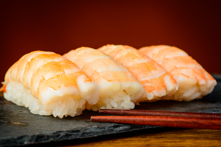 closeup detail of nigiri sushi with shrimps and chopsticks photo