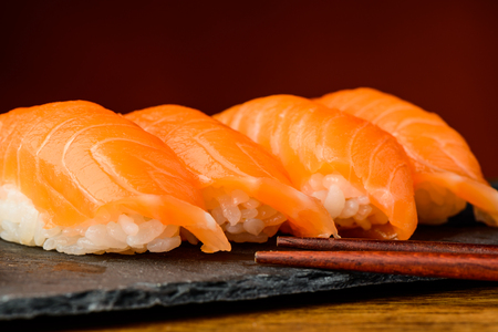 closeup detail of nigiri sushi with salmon and chopsticks photo