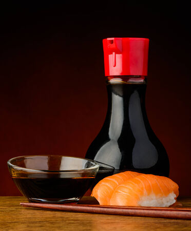 still life with salmon nigiri sushi, soy sauce and chopsticks photo