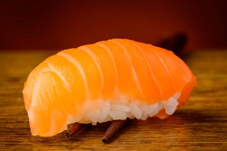 nigiri: closeup detail of nigiri sushi with salmon on chopsticks