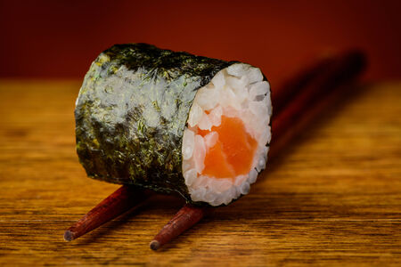 closeup detail of maki sushi roll on chopsticks
