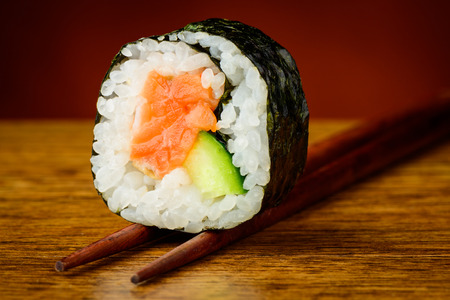 Futomaki sushi roll on chopsticks photo