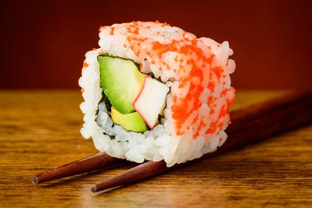 chopstick: uramaki california roll sushi closeup detail on chopsticks Stock Photo