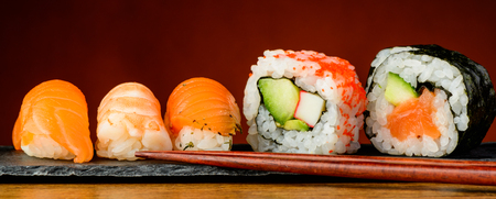 still life with nigiri, uramaki, futomaki sushi and chopsticks photo