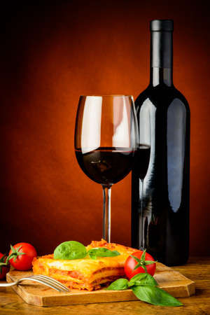 lasagna: traditional lasagna bolognese meal with glass and bottle of red wine  Stock Photo