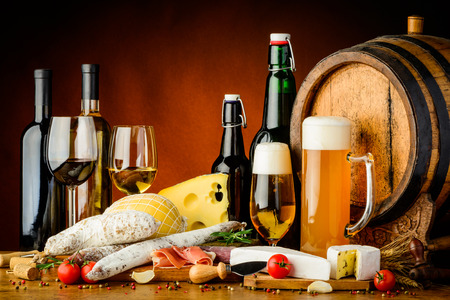 tasting: still life with wine, beer, traditional food, cheese and sausages