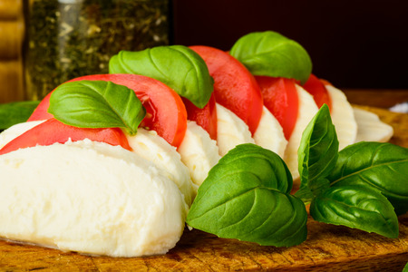 homemade traditional caprese salad with mozzarella cheese, tomatoes and basil