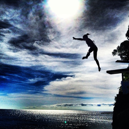 Silhouette of young woman jumping off cliff Reklamní fotografie