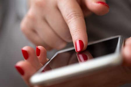 personas: Primer plano de una mano de la mujer utilizando un tel�fono inteligente