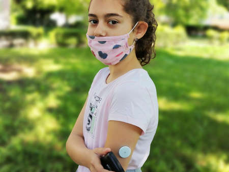 Corona virus and diabetes. Girl with the mask on face checks glucose level in blood with device for continuous glucose monitoring – CGM before entering school. Insulin depend. Diabetes type 1 Archivio Fotografico