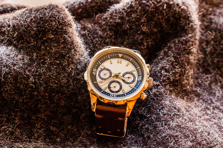 Product photography of a man wrist watch showing time on wool material