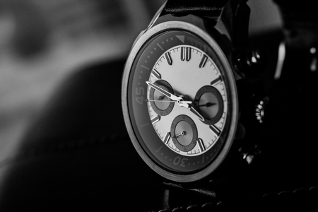 Black and white product photography of a luxury man wrist watch showing time Фото со стока