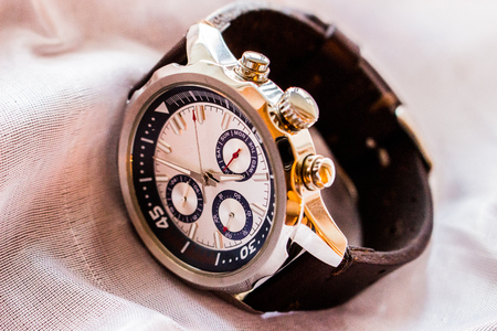 Product photography of a luxury man wrist watch showing time on pink white cloth background