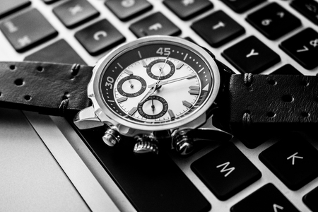 Black and white product photography of a luxury man wrist watch showing time on a computer or laptop keyboard Stock Photo