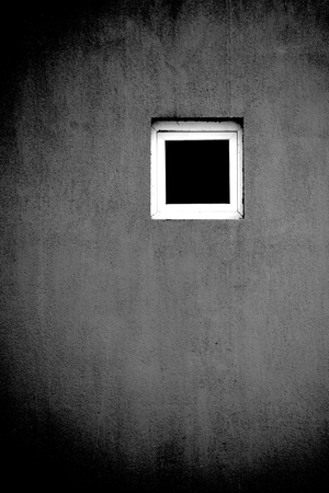 Conceptual window photography. One single window on a wall. Concept of being single, loneliness, solitude, austerity. Artistic black and white photo or photography