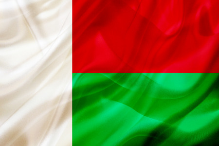 Madagascar country flag symbol on silk or silky waving texture. Smooth fabric or material